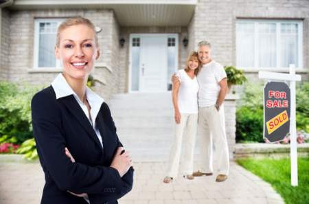 Female real estate agent in front of house with man and woman embracing near For Sale sign